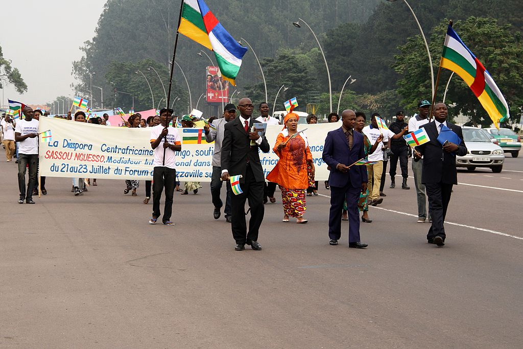People wave flags of the Central African Republic -- the current poorest country in the world -- as they walk to show support to a peace forum