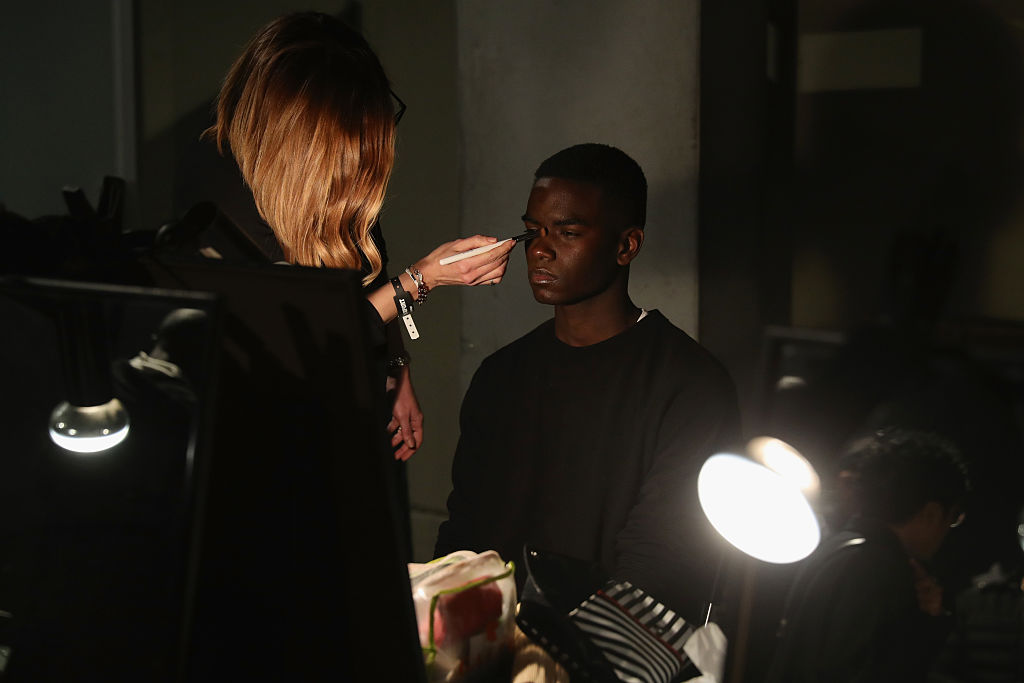 A model has makeup applied backstage ahead of the Plein Sport show