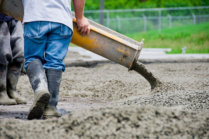 A man is seen pouring cement