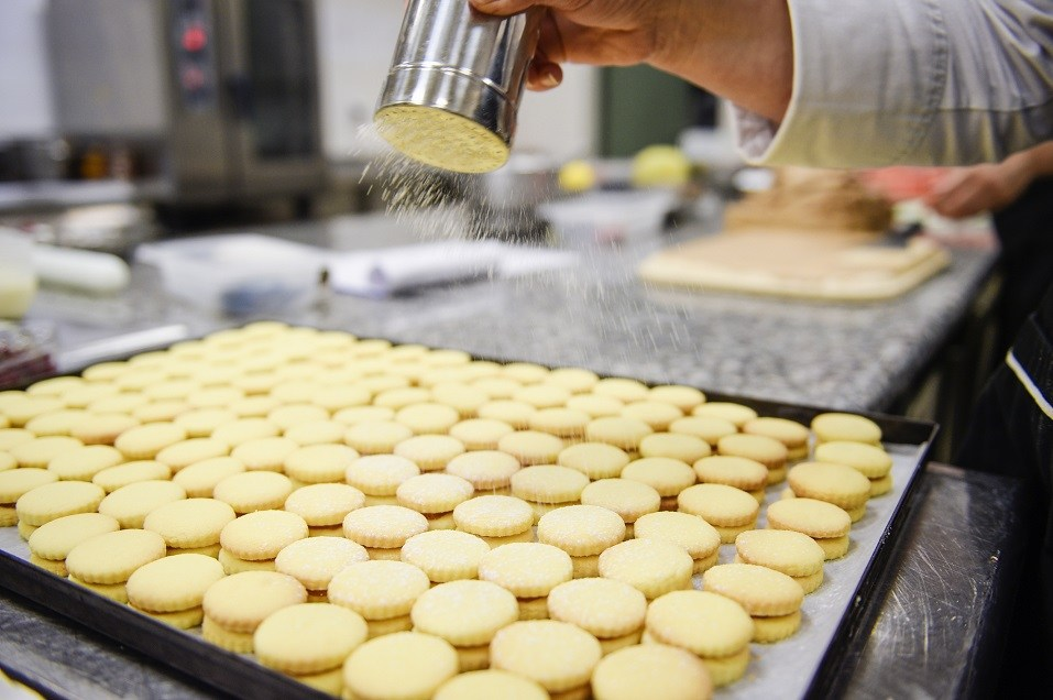 A man makes macaroons in a bakery