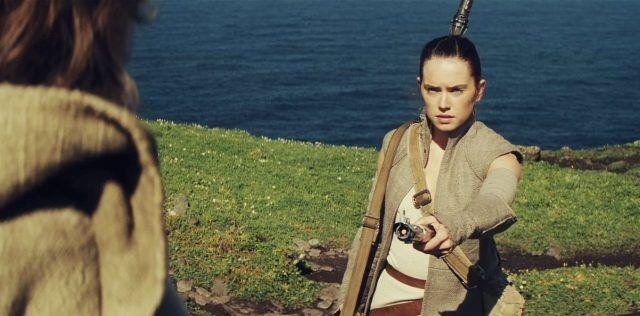 Rey holds a lightsaber while standing on a cliff.