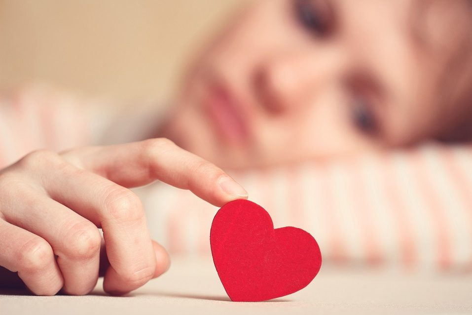 A sad girl looks at a paper heart cutout she holds up with her finger