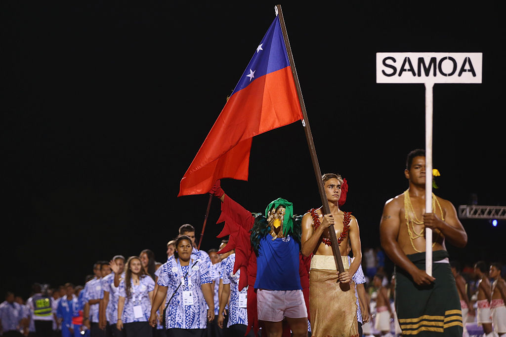 Brandon Schuster of Samoa carries his country flag as he lead the Samoa team