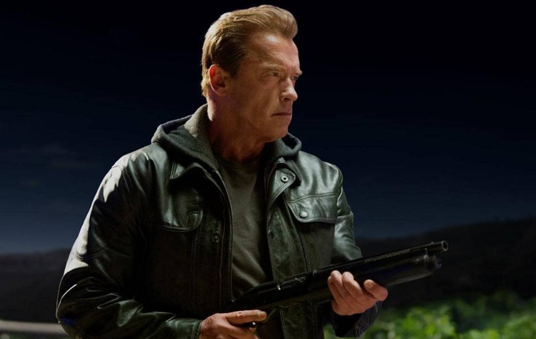Arnold Schwarzenegger in a black leather jacket, about to fire a shotgun