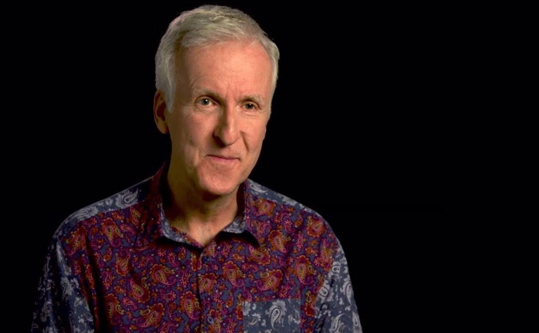 James Cameron is wearing a patterned shirt and talking to the camera.