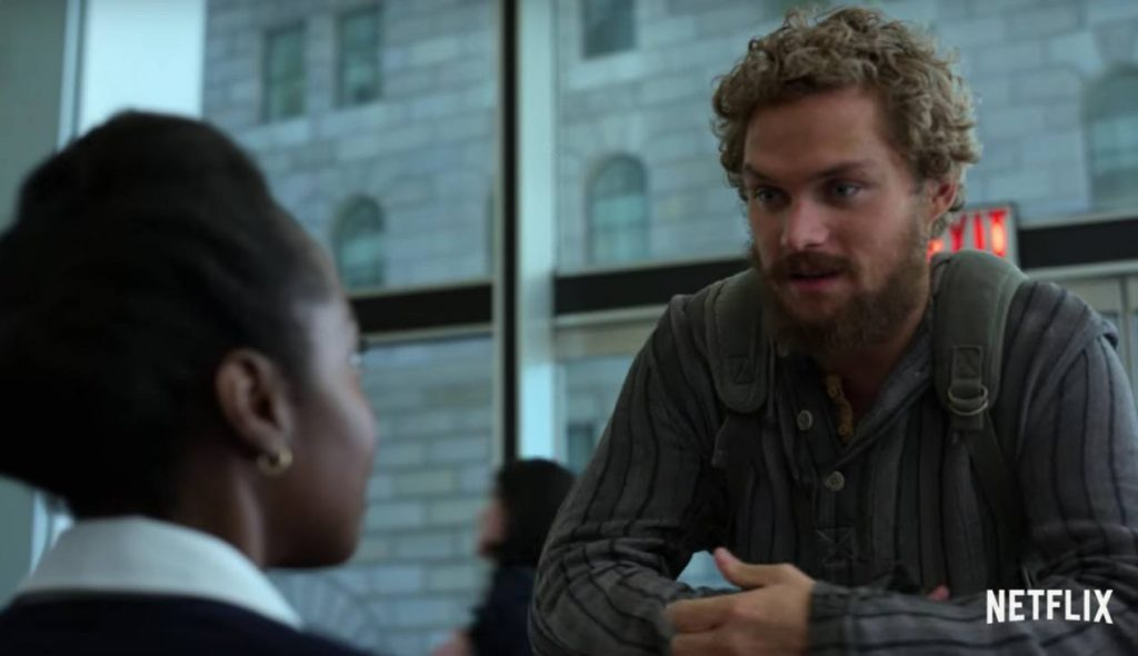 Danny Rand leaning over a desk, wearing tattered clothes and speaking to a receptionist