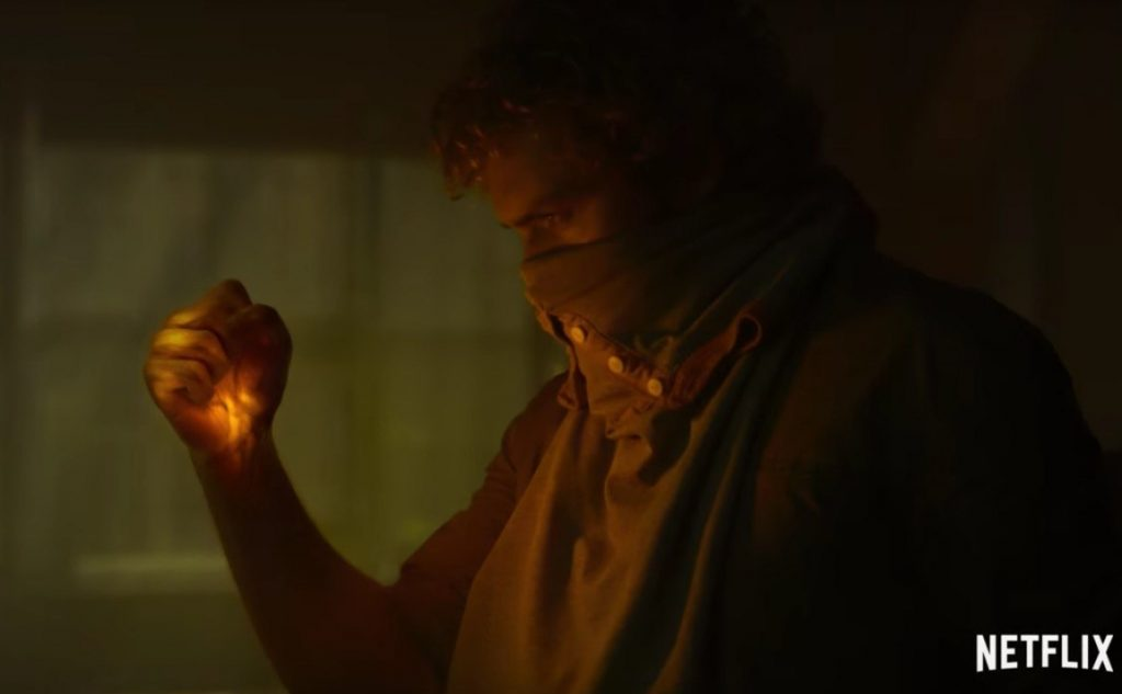 Finn Jones with a glowing fist and covering his mouth with cloth in Iron Fist