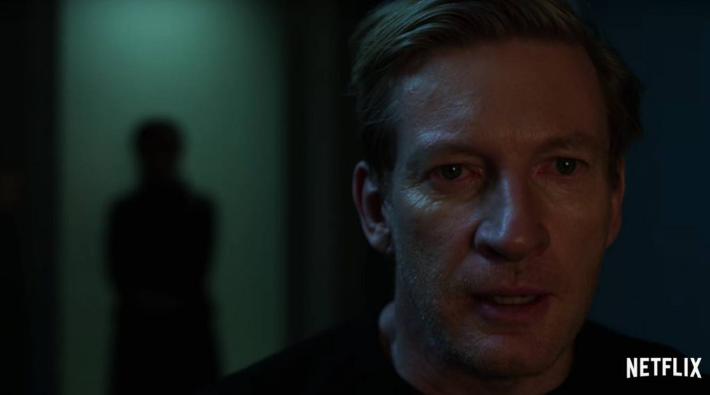 David Wenham looking scared while a mysterious figure lingers in the background on Iron Fist