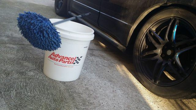 A wash bucket and scrubber mitt next to a car