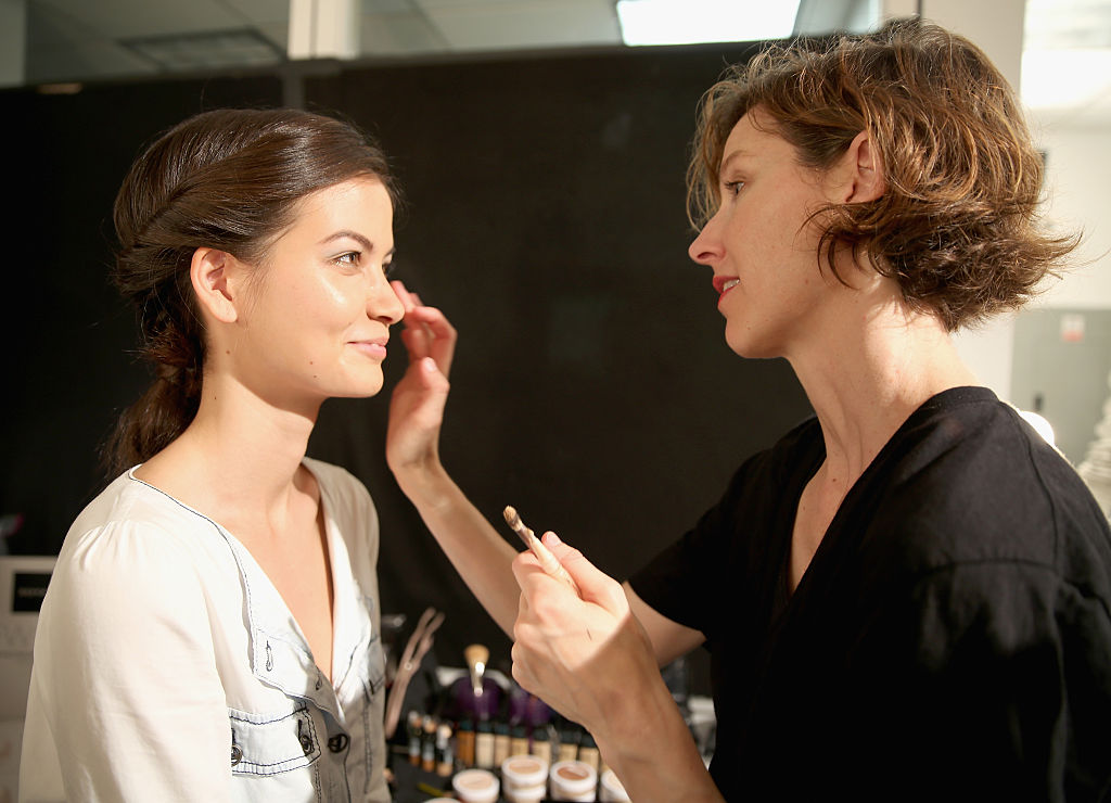 A model prepares her makeup backstage during New York Fashion Week