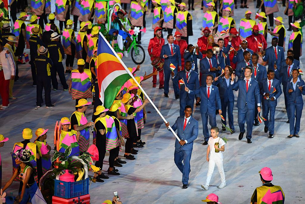 Seychelles' flag bearer Rodney Govinden leads his national delegation