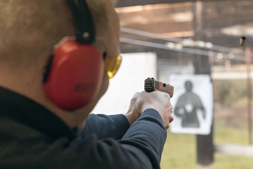 Man aiming pistol at a target in a shooting range