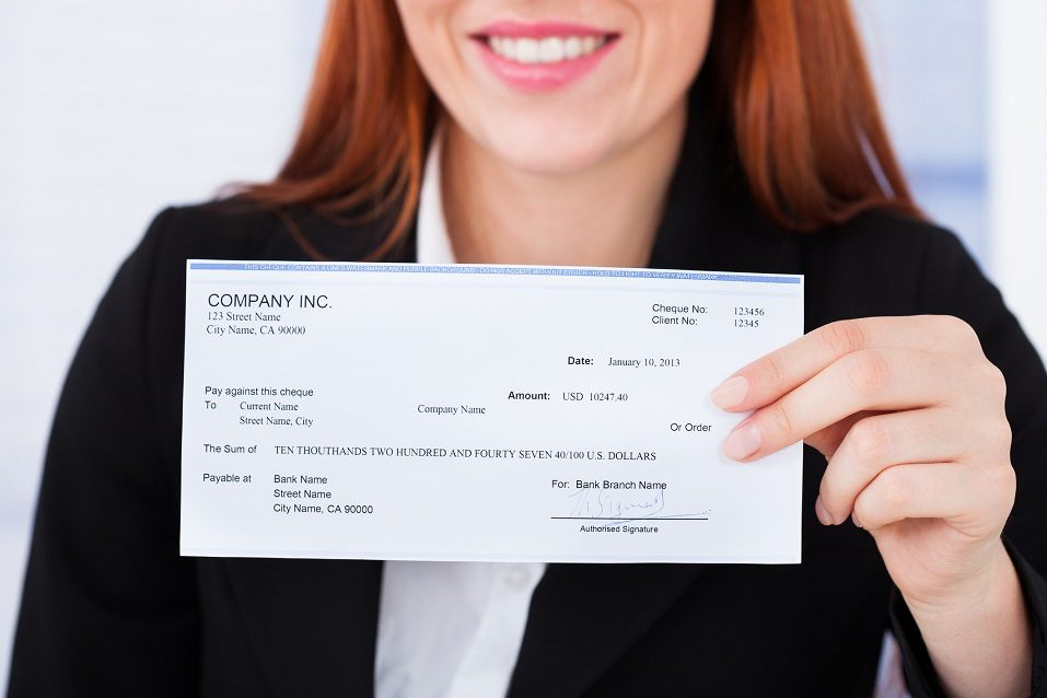 Smiling businesswoman holding check