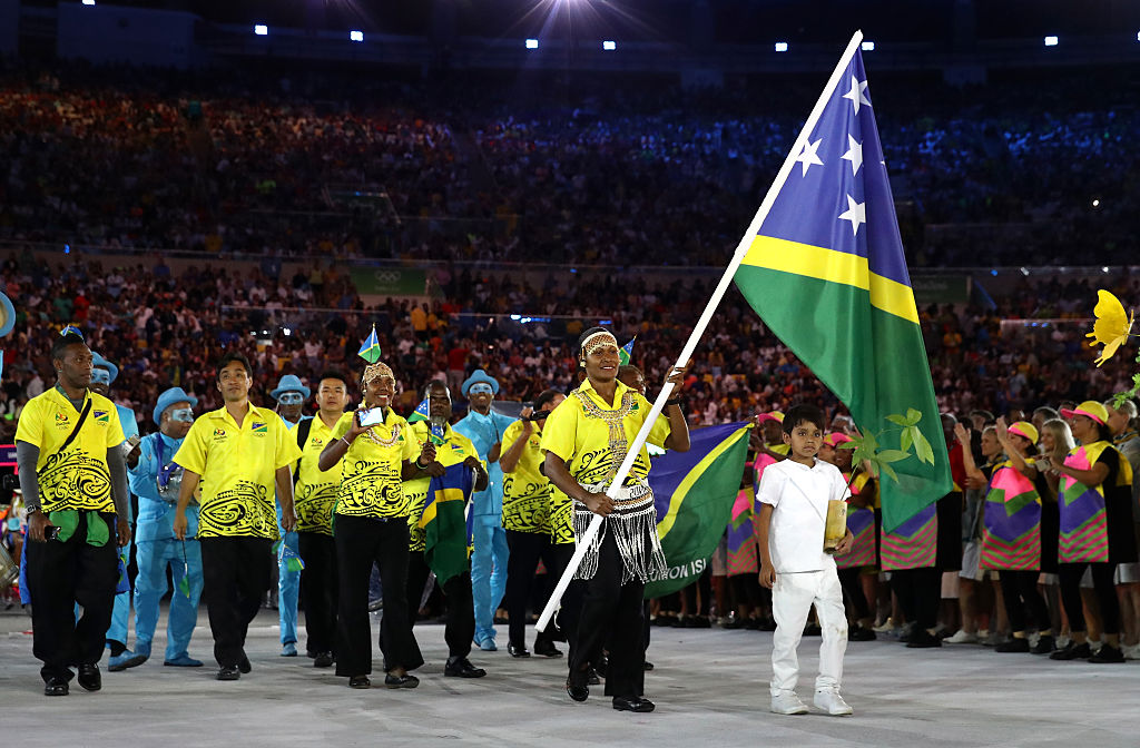 Jenly Wini of the Solomon Islands carries the flag