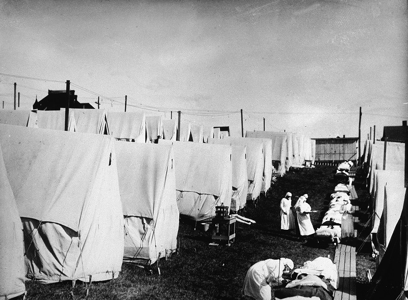 Nurses care for victims of a Spanish influenza epidemic outdoors amidst canvas tents