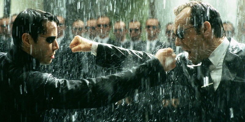 Neo punches a man in the rain in The Matrix Revolutions