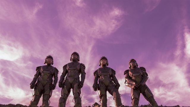 Four people standing together under a purple sky.