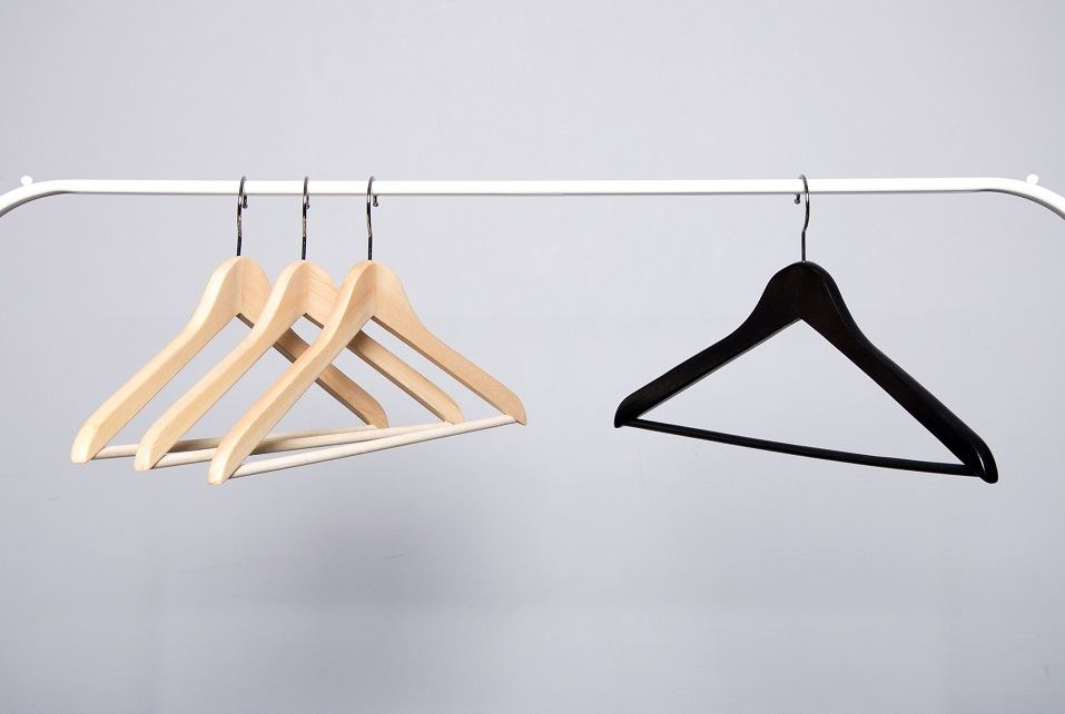 Three beige and one black clothes hangers