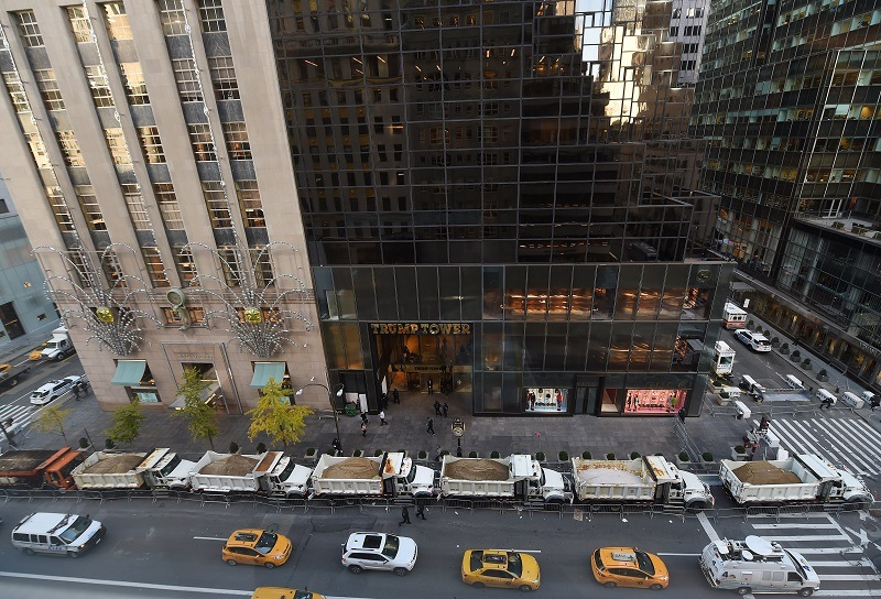 A protective barrier of Sanitation Department trucks parked in front of Trump Tower