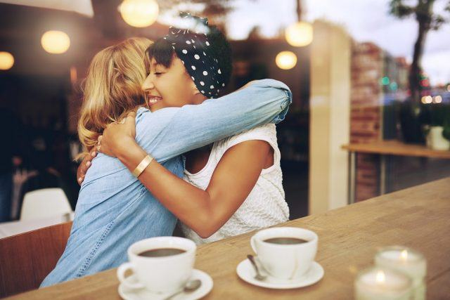 Two women giving each other a hug in a cafe.