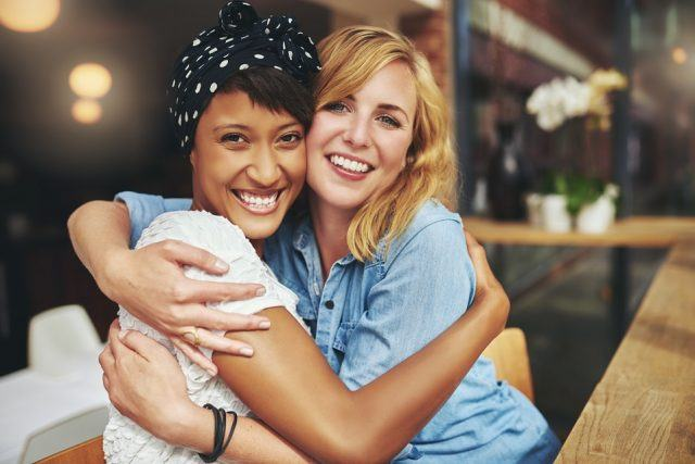 Two happy affectionate young women hugging each other in a close embrace.