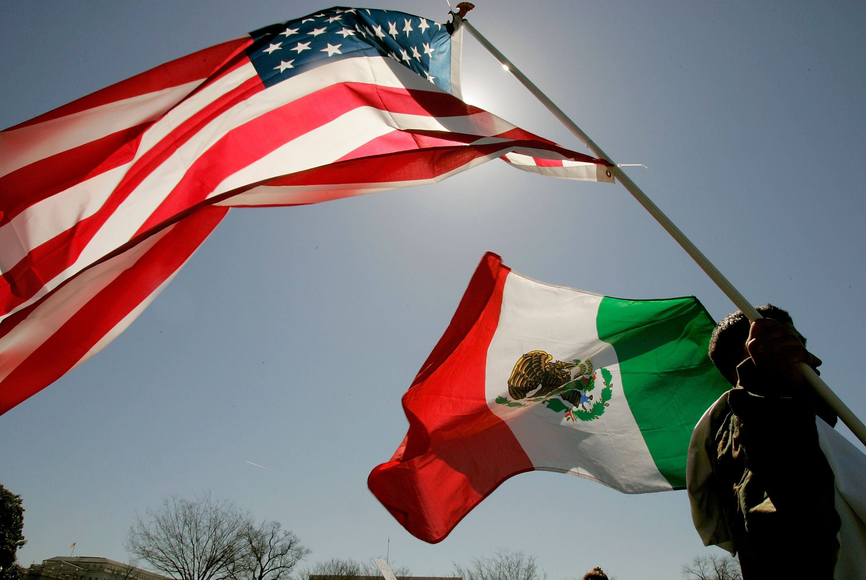 A protester holds the flags of both the United States and Mexico