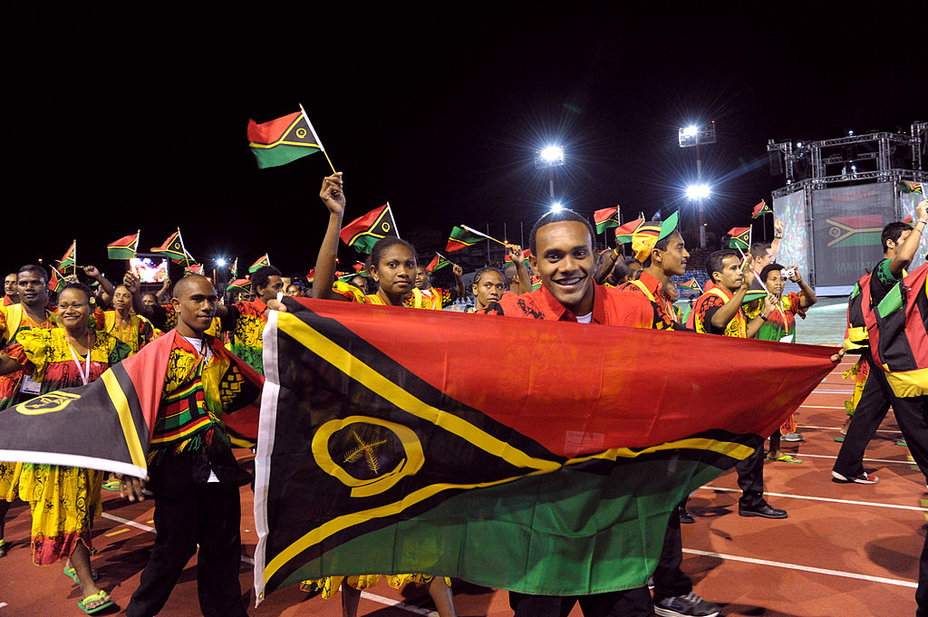 The Vanuatu delegation wave flags as they attend the Olympics