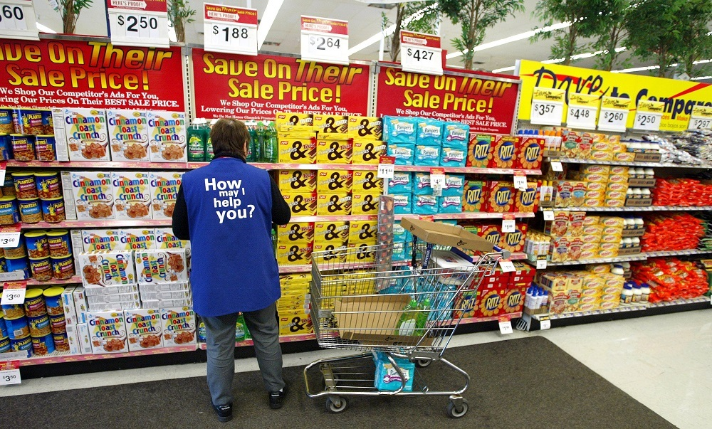 Walmart employee stocking shelves of sale items