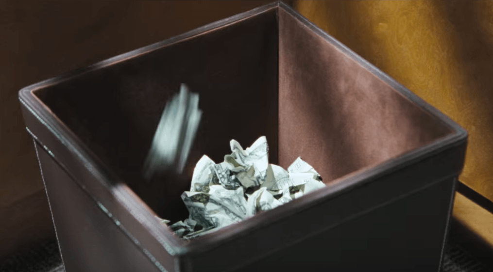 waste money by throwing it into a garbage can