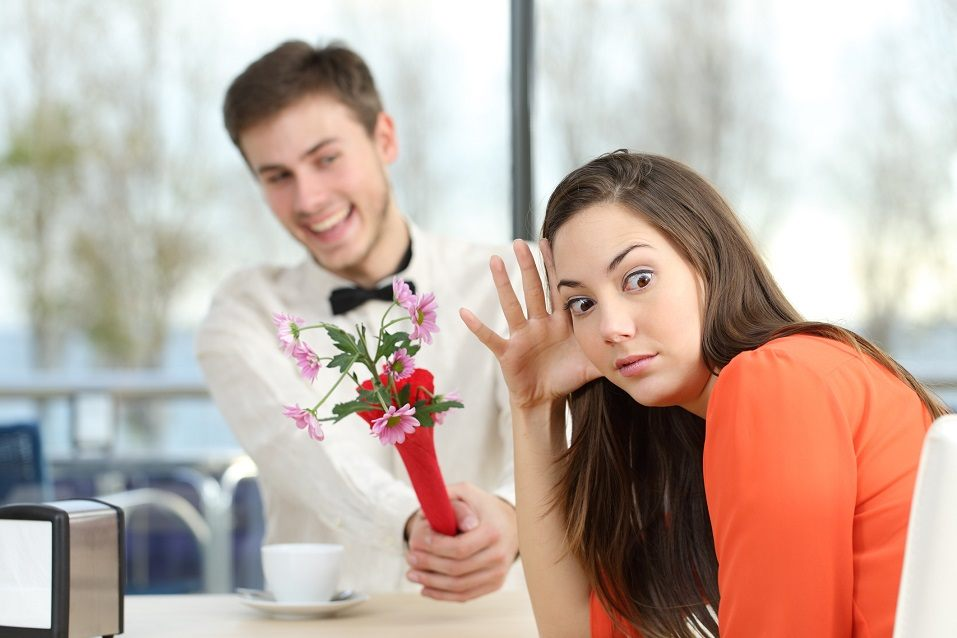 A woman makes an exasperated face on the side as a young man offers her flowers