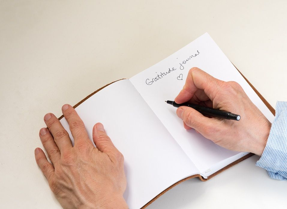 A middle aged woman writes in her gratitude journal