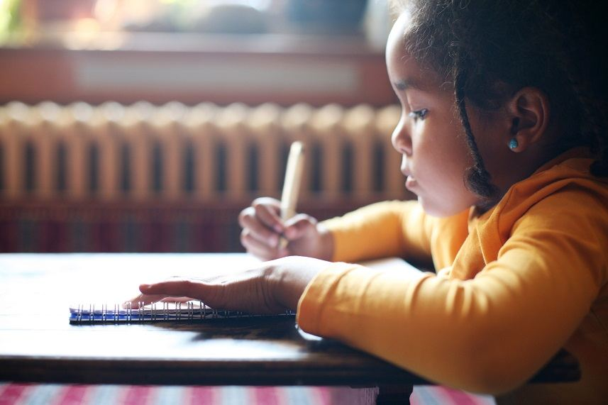 Little African-American girl writing in the classroom