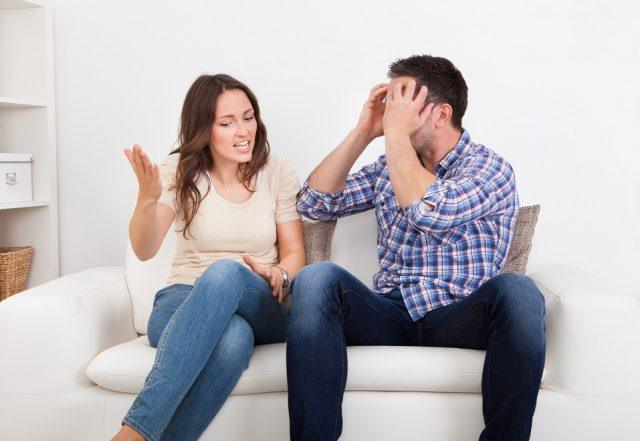 A frustrated couple sits on a couch during a quarrel.