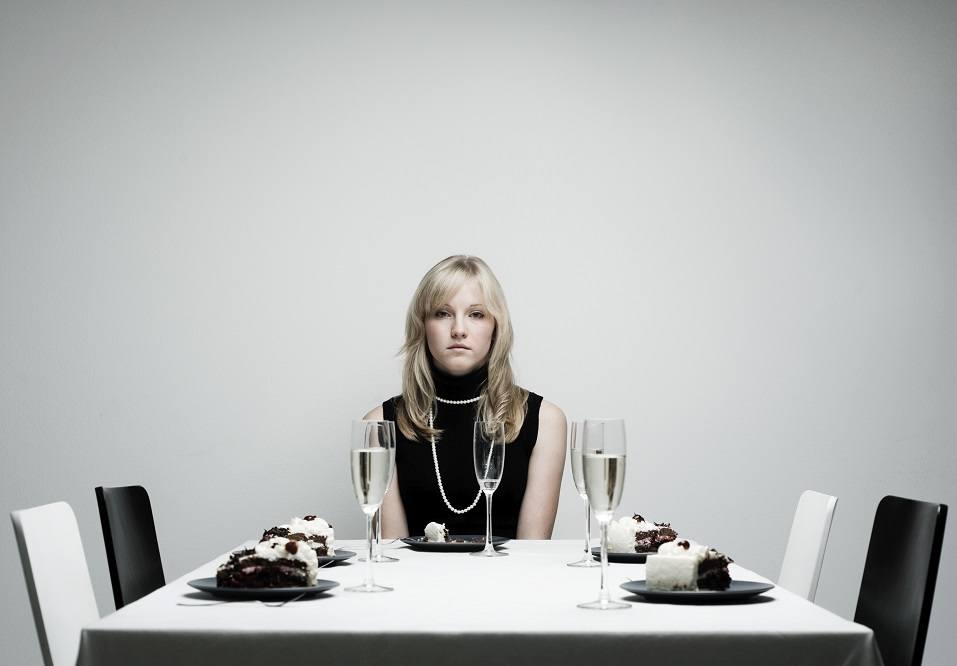 Woman sits alone at dinner table