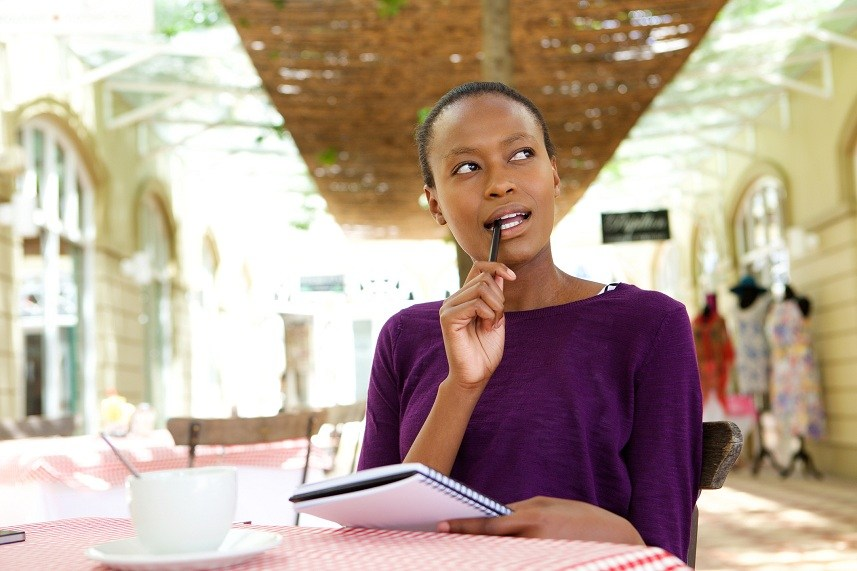 A young African-American woman sits at a table in a cafe