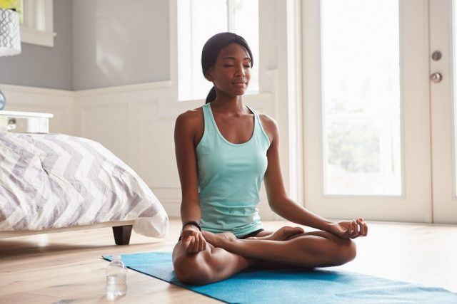 A young woman meditates on top of a yoga mat in her bedroom.