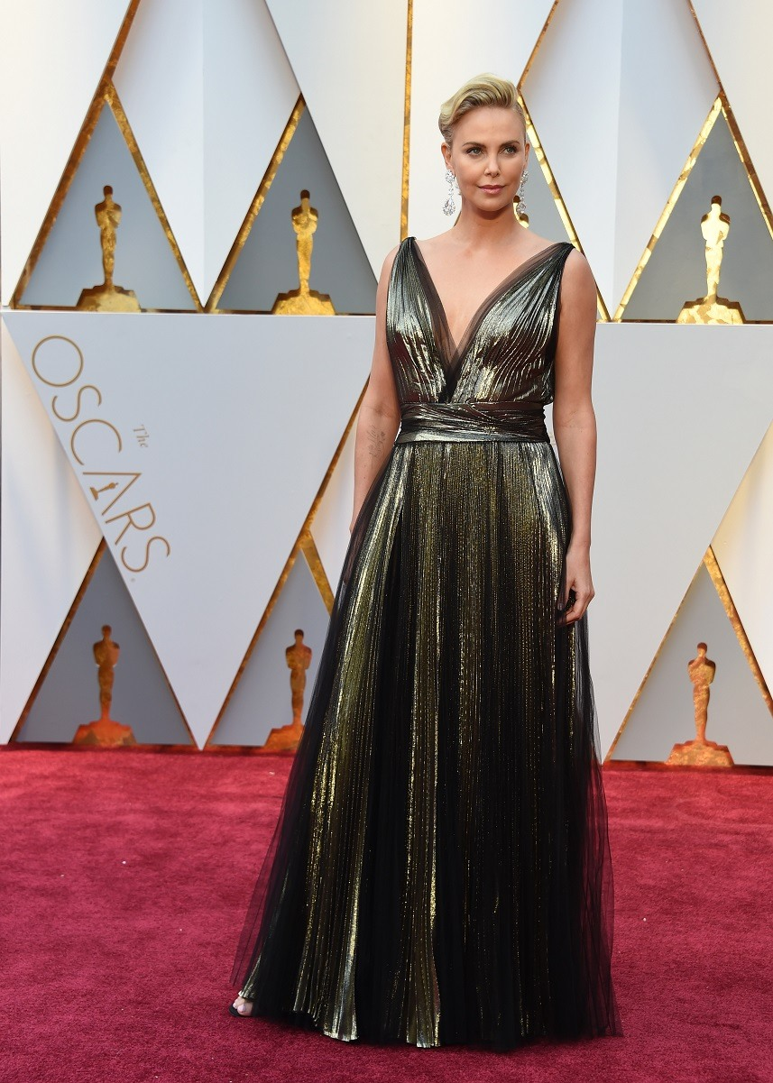 Charlize Theron poses as she arrives on the red carpet for the 89th Oscars