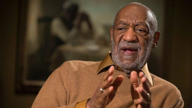 Bill Cosby wearing a tan collared shirt, with his hands out and speaking in an interview.