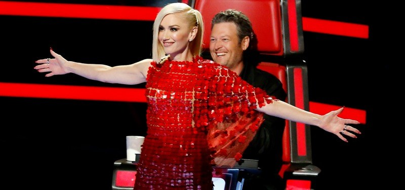 Gwen Stefani stands in front of Blake Shelton with her arms stretched out on The Voice.