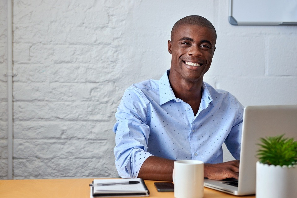 An African-American young business man works on his laptop