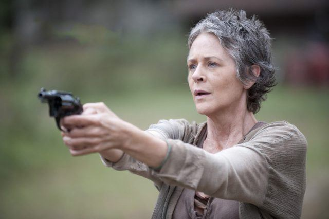 Carol holds up a gun while staring straight ahead.