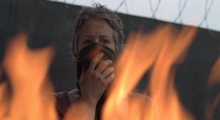 Carol stands and watches flames in a scene from 'The Walking Dead'