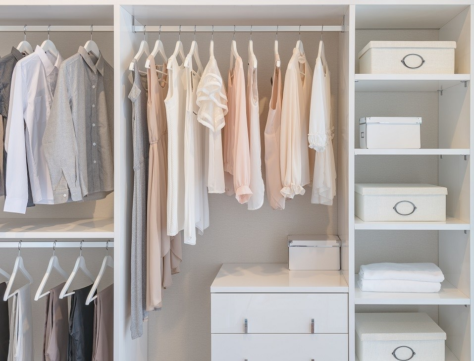 clothes hanging on rail in white wardrobe