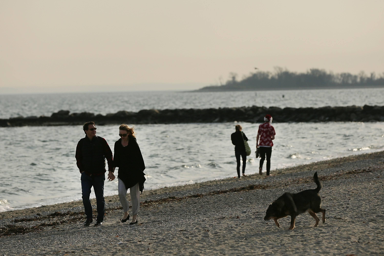 Couples walk along a Connecticut beach