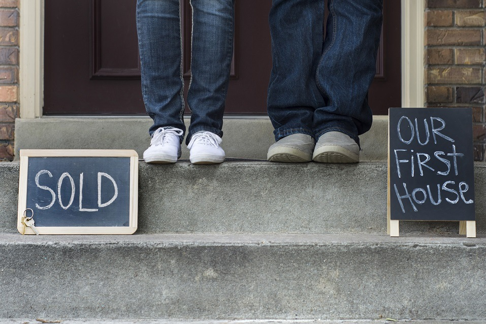 couple's feet in front of house