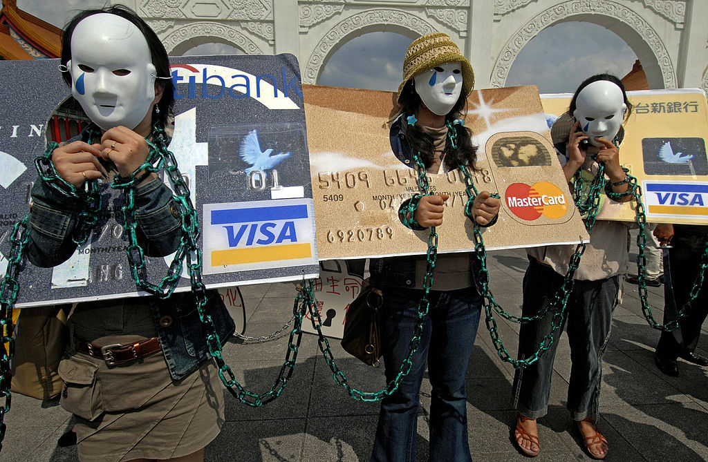 """Consumers who are in credit card debt, referred to as """"credit card slaves,"""" take part in a demonstration."""