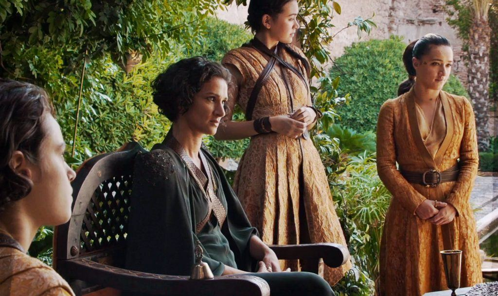 Ellaria Sand sits in her chair, surrounded by her supporters on a nice day in Game of Thrones