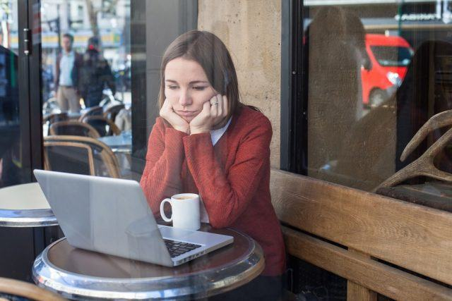 woman looking sadly at her computer while drinking coffee outside