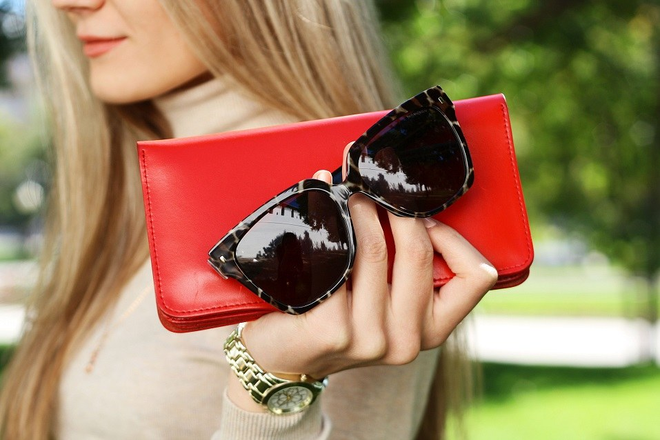 Woman hold red purse clutch in hand with black trendy sunglasses