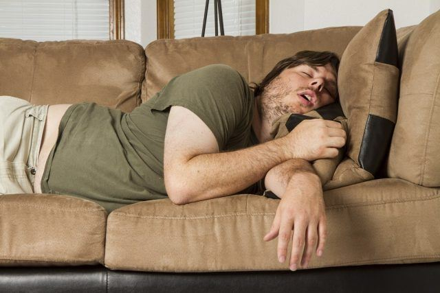 A guy sleeping on the couch with his mouth open.